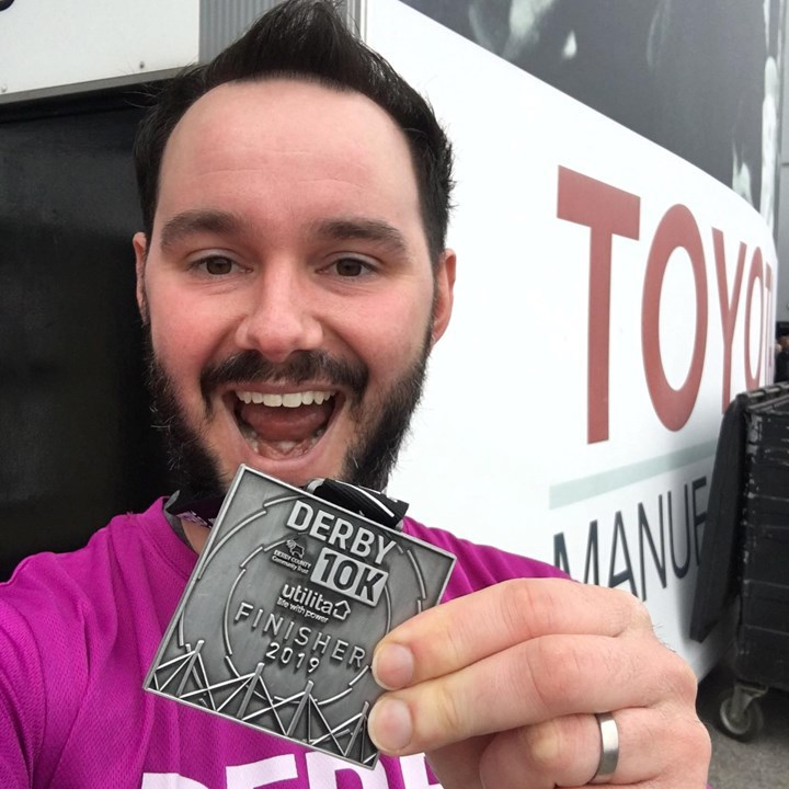 Alan poses with a running medal after running for alzheimer's
